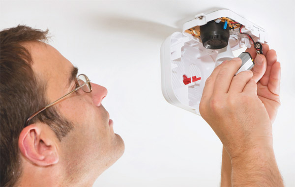 Man changing smoke detector
